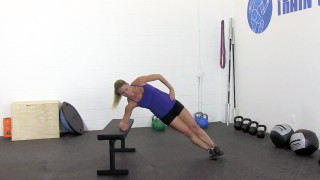 Female exercising - bench side plank hip raise