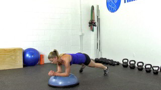 Female exercising - bosu plank alternating toe taps