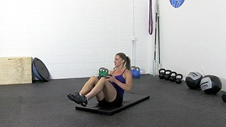 Female exercising - dumbbell seated trunk twist