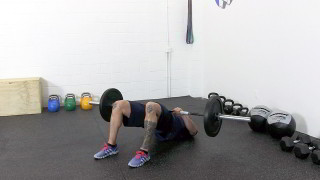 Male exercising - barbell glute bridge