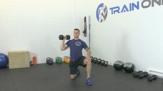 Male exercising - kneeling dumbbell shoulder press
