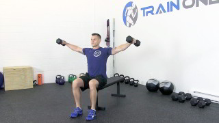 Male exercising - seated dumbbell shoulder raise