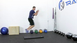 Male exercising - broad jumps over mat