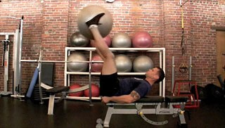 Picture of a male doing Double Leg Drop w/ Stability Ball Exercise