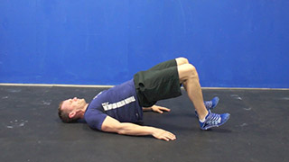 Male exercising - glute bridges