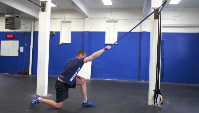 Male exercising - kneeling lat stretch