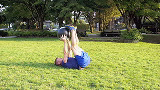 Male exercising - outdoor medicine ball leg drops