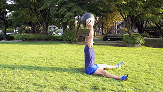 Male exercising - outdoor medicine ball sit-ups