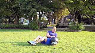 Male exercising - outdoor medicine ball twist