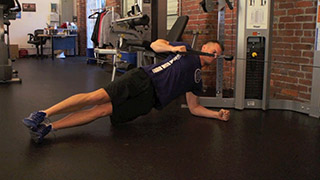 Male exercising - side plank cable rows