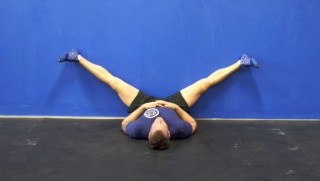 Male exercising - splits against the wall
